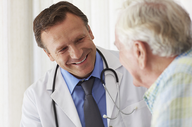 An elderly man receiving a checkup from his doctor