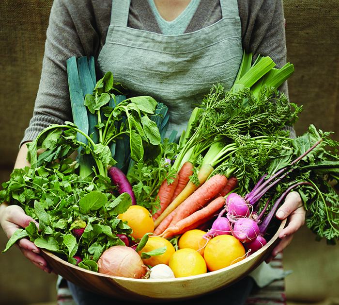 lady holding bowl of vegetables