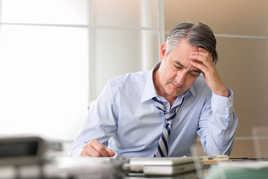 man sitting at desk with hand on head showing signs of stress