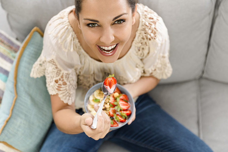 younf woman eating a bowl of fruits