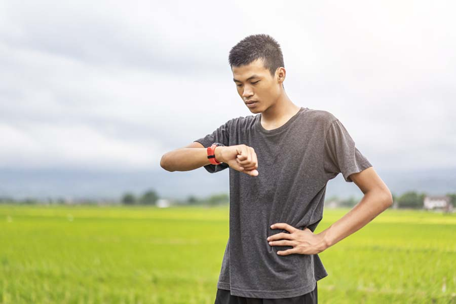 male asian teenager checking heart rate