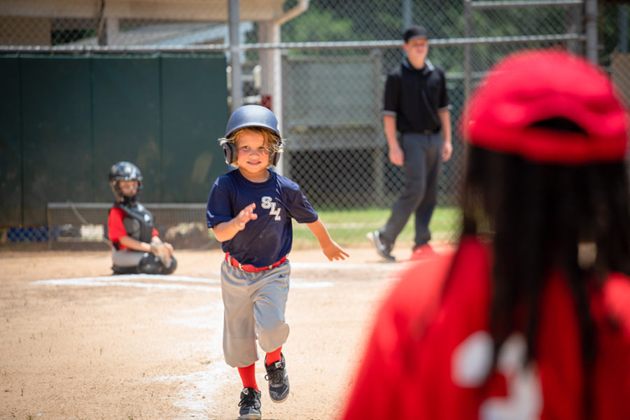 young bog running to first base at a softball game