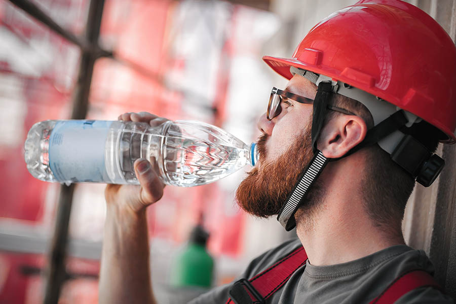 male construction worker drinking water